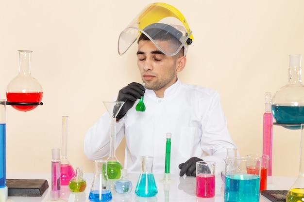 Młody chemik mężczyzna w białym specjalnym garniturze przed stołem z kolorowymi roztworami pracującymi z nimi na biurku z kremem
