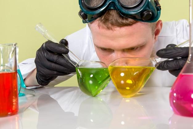 Młody chemik tryna z przodu rozróżnia zielone i żółte chemikalia