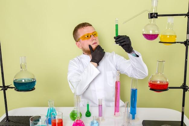 Młody chemik z przodu patrząc na zielony środek chemiczny w pomarańczowych okularach ochronnych