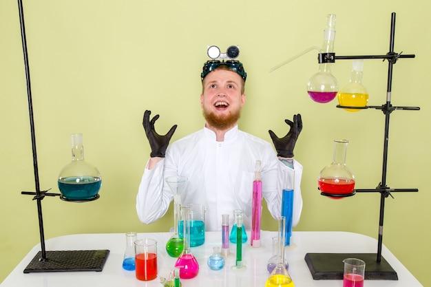 Młody chemik z przodu znajduje nową substancję chemiczną do użycia przeciwko swoim wrogom