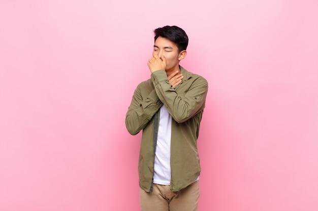Młody chińczyk czuje się chory z bólem gardła i objawami grypy, kaszel z ustami pokrytymi ścianą koloru