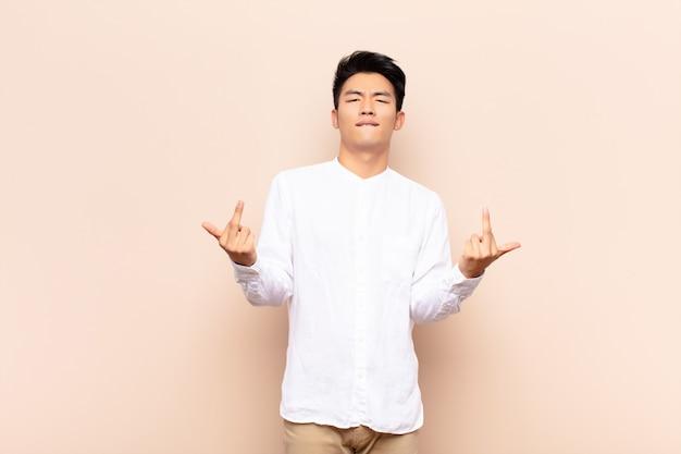 Młody chińczyk czuje się prowokacyjnie, agresywnie i nieprzyzwoicie, machając środkowym palcem, z buntowniczym nastawieniem na płaskiej, kolorowej ścianie