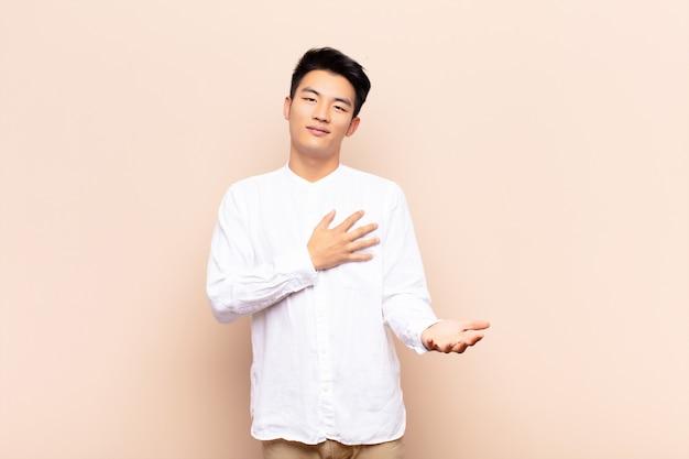 Młody chińczyk czuje się szczęśliwy i zakochany, uśmiechając się jedną ręką obok serca, a drugą wyciągnął do przodu o ścianę koloru płaskiego