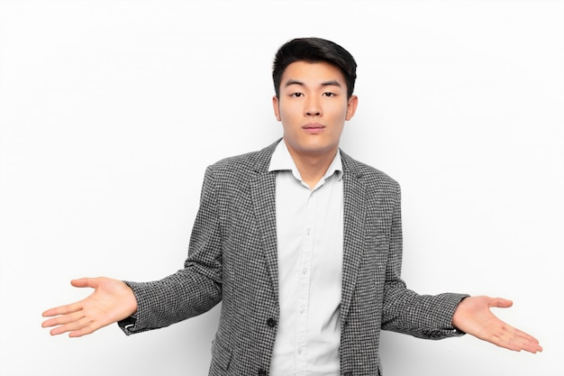 Młody chińczyk czuje się zdziwiony i zdezorientowany, niepewny prawidłowej odpowiedzi lub decyzji, próbując dokonać wyboru na płaskiej ścianie koloru