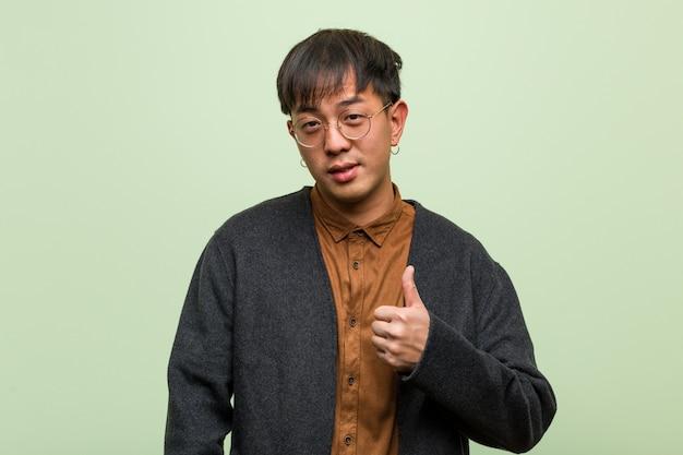 Młody chińczyk jest ubranym chłodno ubrania styl przeciw zieleni