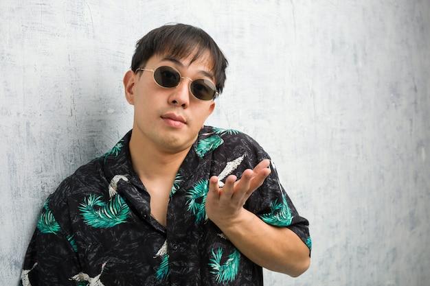 Młody chińczyk jest ubranym lato strój wątpi w ramionach i wzrusza ramionami