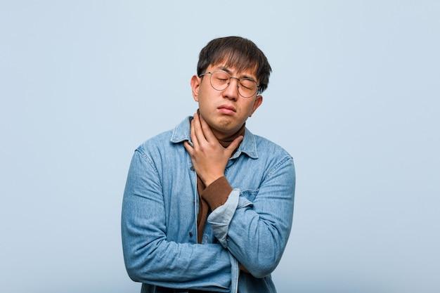 Młody chińczyk kaszle, choruje z powodu wirusa lub infekcji