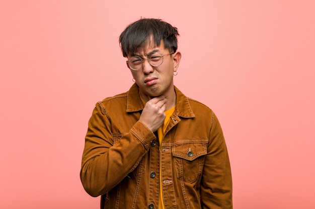 Młody chińczyk ma na sobie kaszel, chory z powodu wirusa lub infekcji