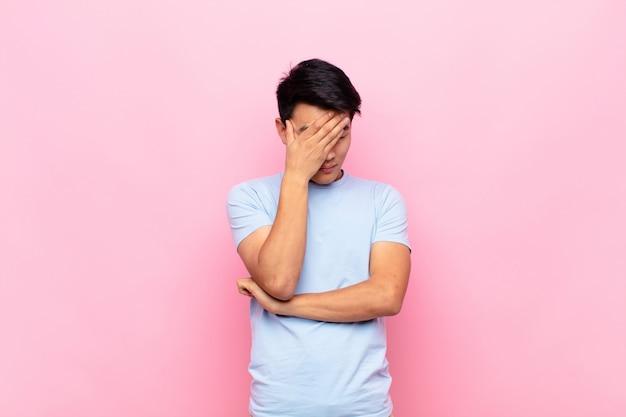 Młody chińczyk wyglądający na zestresowanego, zawstydzonego lub zdenerwowanego, z bólem głowy, wykrzywioną twarzą z ręką na płaskiej ścianie koloru