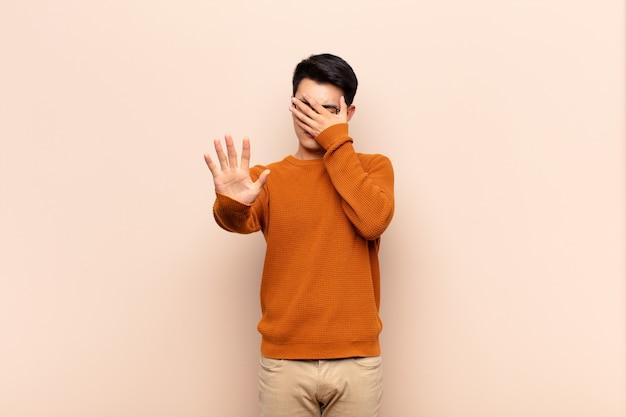 Młody chińczyk zakrywa twarz ręką i stawia drugą rękę z przodu zatrzymywać, odmawiając fotografii lub obrazka przeciw płaskiej kolor ścianie