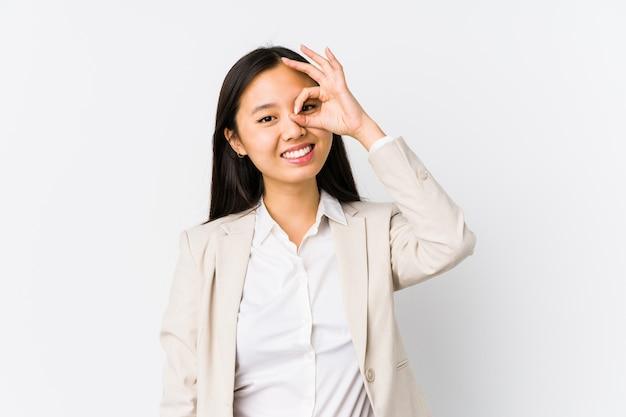 Młody chiński biznes kobieta na białym tle podekscytowany utrzymując ok gest na oko.