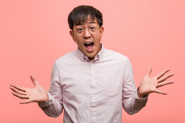 Młody chiński człowiek świętuje zwycięstwo lub sukces