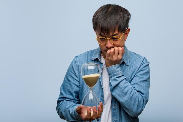 Młody chiński człowiek trzyma zegar piasku obgryzanie paznokci, nerwowy i bardzo niespokojny