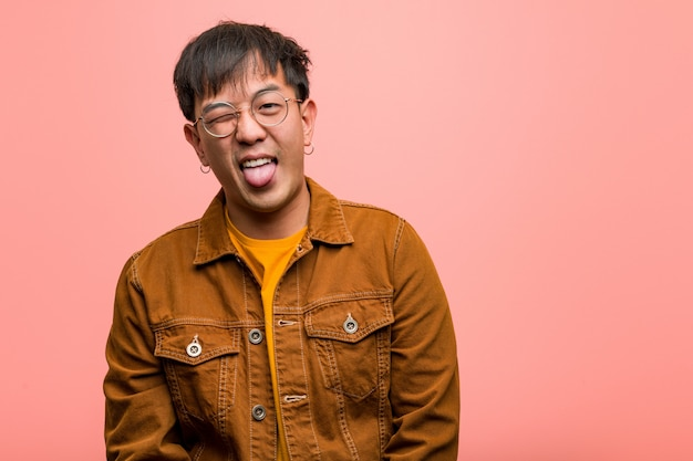 Młody chiński człowiek ubrany w zabawną kurtkę i przyjazny język pokazując