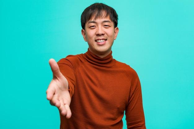 Młody chiński człowiek wyciąga rękę, aby kogoś przywitać