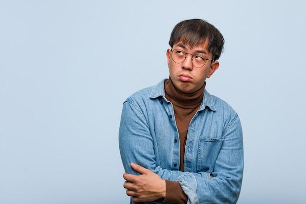 Młody chiński człowiek zmęczony i znudzony