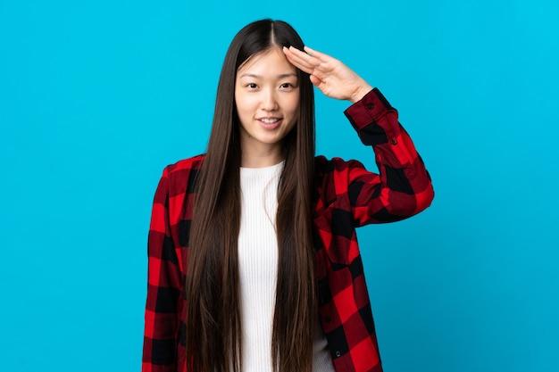 Młody chiński dziewczyna na niebiesko salutowanie ręką z happy wypowiedzi