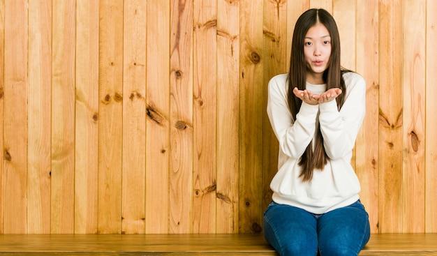 Młody chiński kobieta siedzi na drewniane miejsce, składając usta i trzymając dłonie, aby wysłać pocałunek powietrza.
