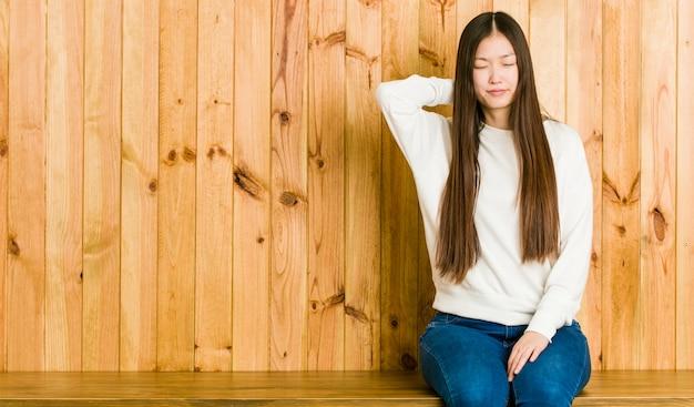 Młody chiński kobieta siedzi na drewnianym miejscu cierpi ból szyi z powodu siedzącego trybu życia.