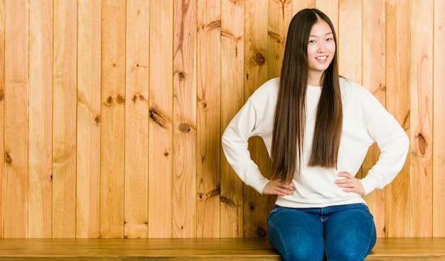Młody chiński kobiety obsiadanie na drewnianym miejscu ufny utrzymuje ręce na biodrach.