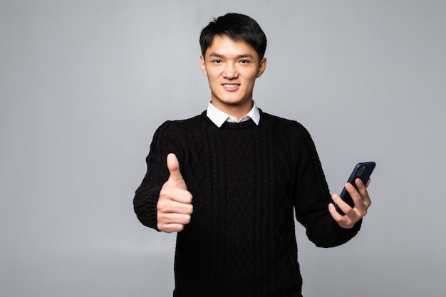 Młody chiński mężczyzna opowiada na smartphone stać szczęśliwy z dużym uśmiechem robi ok znakowi, kciuk up z palcami, znakomity podpisuje odosobnioną biel ścianę