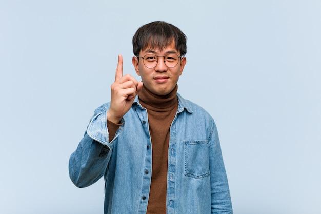 Młody chiński mężczyzna pokazuje liczbę jeden