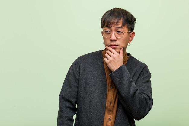 Młody chiński mężczyzna przeciw zielonej ścianie