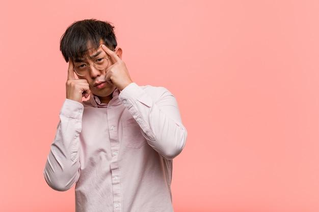 Młody chiński mężczyzna robi koncentracyjnemu gestowi