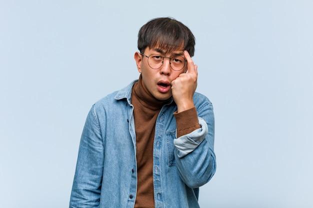 Młody chiński mężczyzna robi rozczarowanie gestowi z palcem