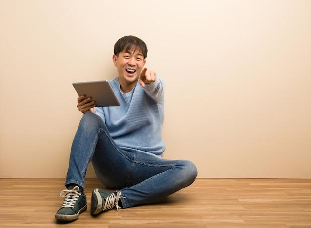 Młody chiński mężczyzna siedzi przy użyciu tabletu marzy o osiągnięciu celów i zamierzeń