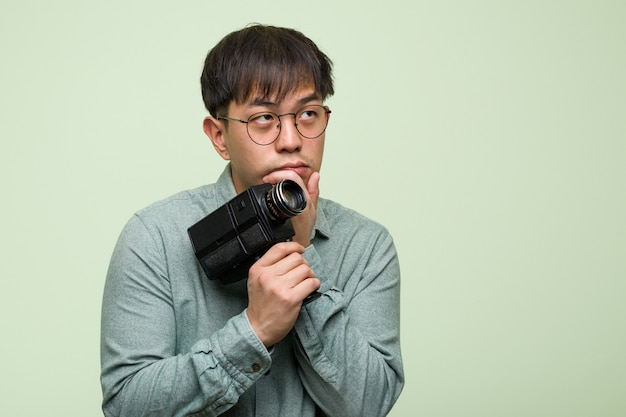 Młody chiński mężczyzna trzyma rocznika kamerę wątpić i wprawiać w zakłopotanie