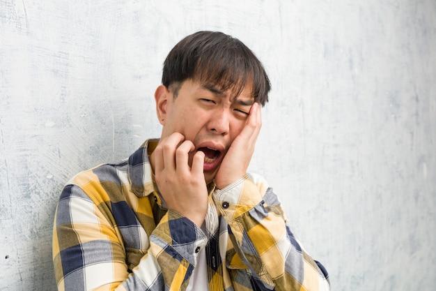 Młody chiński mężczyzna twarzy zbliżenie desperacki i smutny