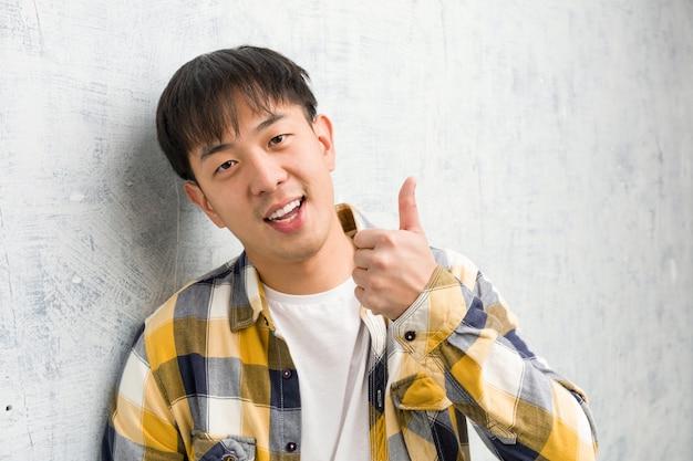 Młody chiński mężczyzna twarzy zbliżenie ono uśmiecha się i podnosi kciuk up