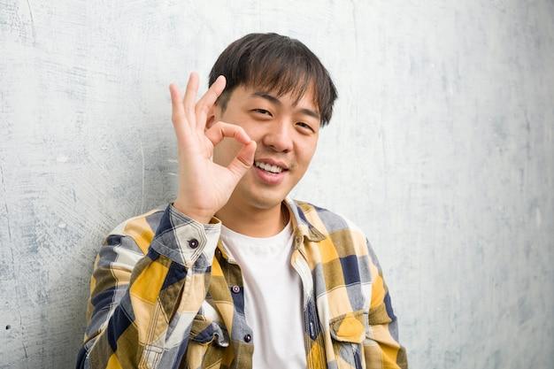 Młody chiński mężczyzna twarzy zbliżenie rozochocony i ufny robi ok gestowi