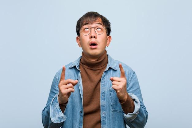 Młody chiński mężczyzna zaskakujący wskazywać w górę przedstawienia coś