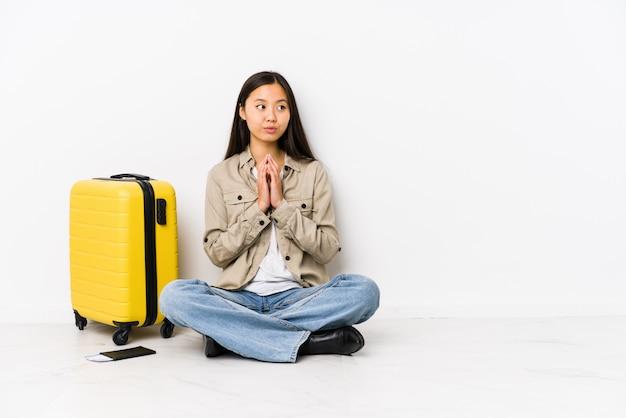 Młody chiński podróżnik kobieta siedzi, trzymając karty pokładowe, tworząc plan na uwadze, ustanawiając pomysł.