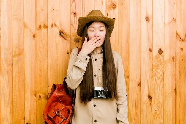 Młody chiński podróżnik kobiety ziewanie pokazuje zmęczonego gesta nakrywkowego usta ręką.