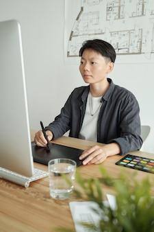 Młody chiński projektant z rysikiem rysującym na ekranie tabletu