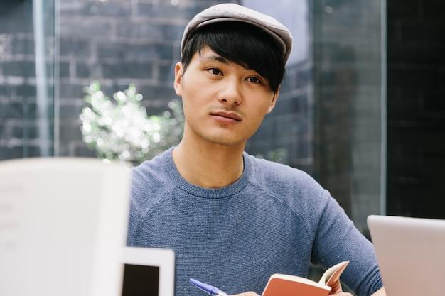 Młody chiński przedsiębiorca słucha swoich kolegów pracujących w coworkingowej espace