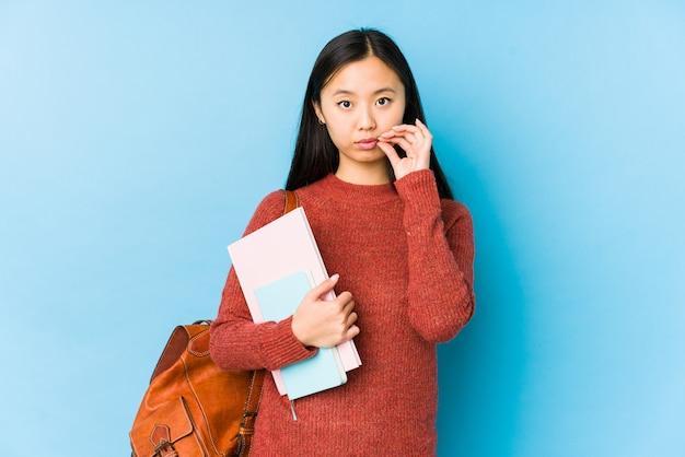 Młody chiński student kobieta na białym tle z palcami na ustach, utrzymując tajemnicę.