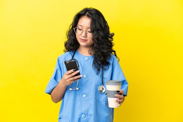 Młody chirurg lekarz azjatycka kobieta odizolowana na żółtym tle trzymająca kawę na wynos i telefon komórkowy