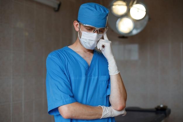 Młody chirurg w niebieskim mundurze medycznym w ochronnej białej masce i gumowych rękawiczkach stoi w szpitalu i myśli