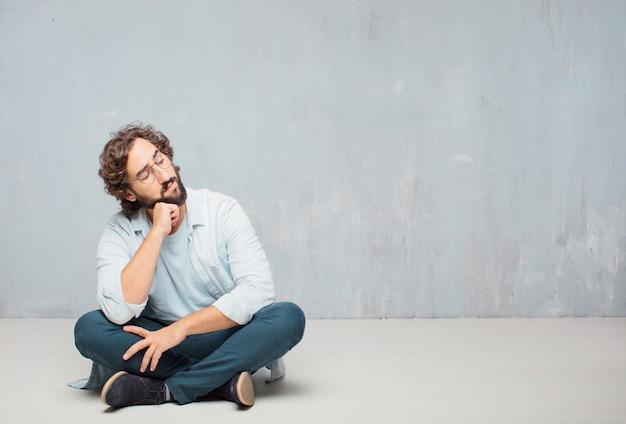 Młody chłodno brodaty mężczyzna obsiadanie na podłoga. tło grunge ściany