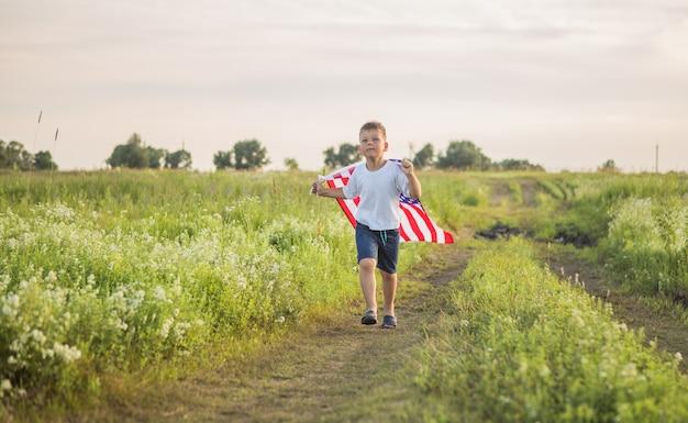 Młody chłopak 4 lata trzyma amerykańską flagę o zachodzie słońca w polu