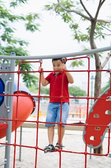 Młody chłopak azjatyckich wspiąć się na płot czerwony liny i szary pasek za rękę do ćwiczeń na placu zabaw pod wielkim drzewem.