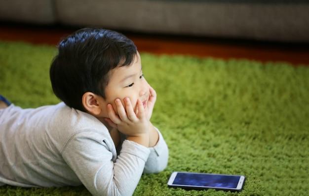 Młody chłopak bawi się sam w salonie