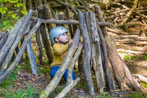 Młody chłopak bawi się w lesie latem lub wiosną.
