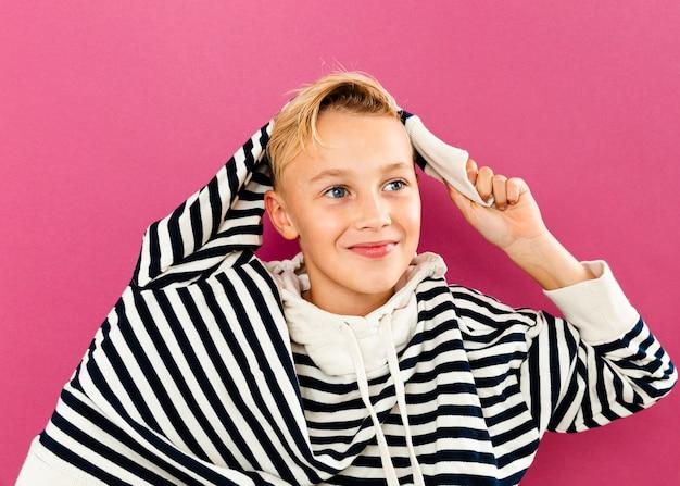 Młody chłopak bawi się z kapturem, który ma na sobie