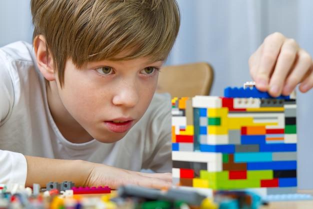 Młody chłopak bawi się zabawkami konstrukcyjnymi z tworzyw sztucznych w domu.