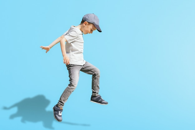 Młody chłopak biegnie w skoku na ulicy na jasnym niebieskim tle